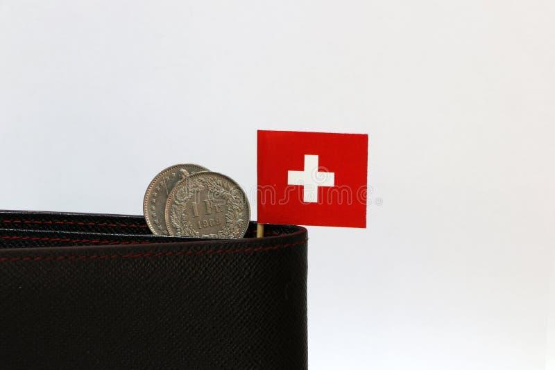 Två mynt av en schweizisk franc och mini- Schweiz flaggapinne på den svarta plånboken med vit bakgrund Franc Schweiz pengar royaltyfria foton