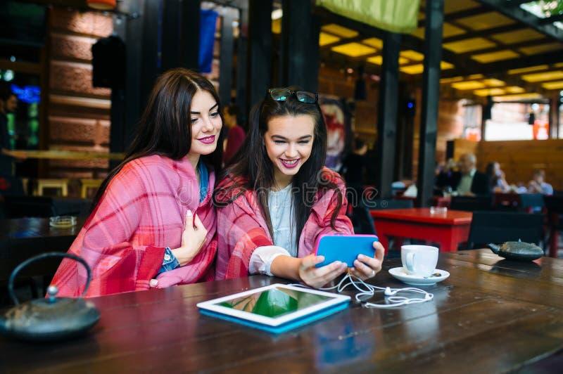 Två nära vänner gör selfie i kafét royaltyfri bild