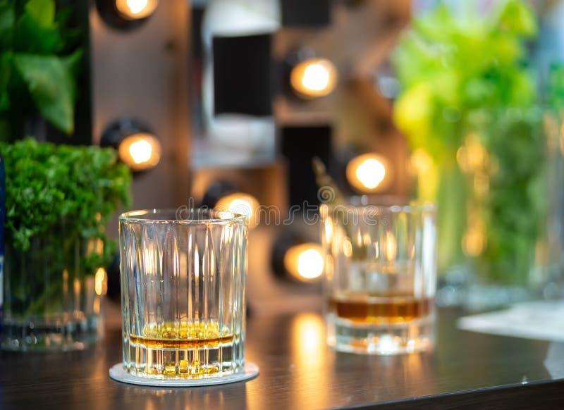 Två nästan tomma exponeringsglas av whisky arkivfoto