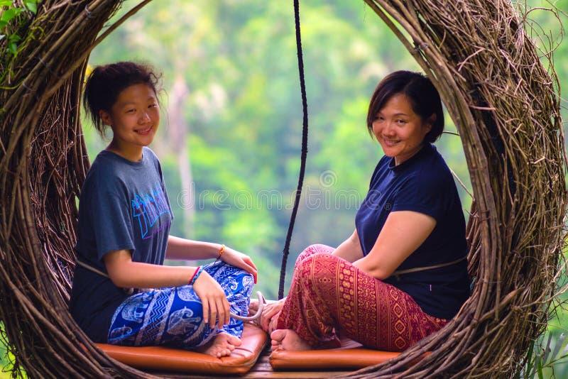 Två nätta asiatiska kvinnor som sitter på sugrörredet, Ubud, Bali, 05 01 2019 close upp arkivfoto