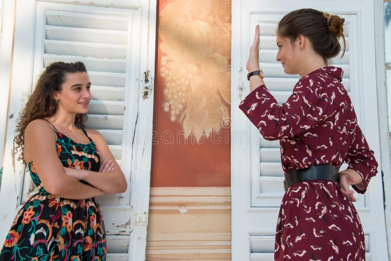Två nätta flickor visar att fingrarna korsade handtecknet royaltyfria foton
