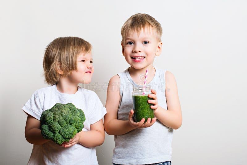 Två nätta gyckelungar med gröna smoothies och broccoli Helthy arkivfoton