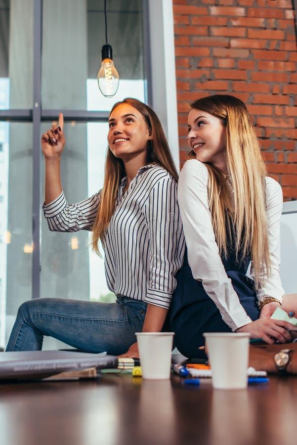 Två nätta kvinnliga studenter som tillsammans sitter på skrivbordet i klassrum, en flicka som pekar på den ljusa kulan, gillar at royaltyfria foton