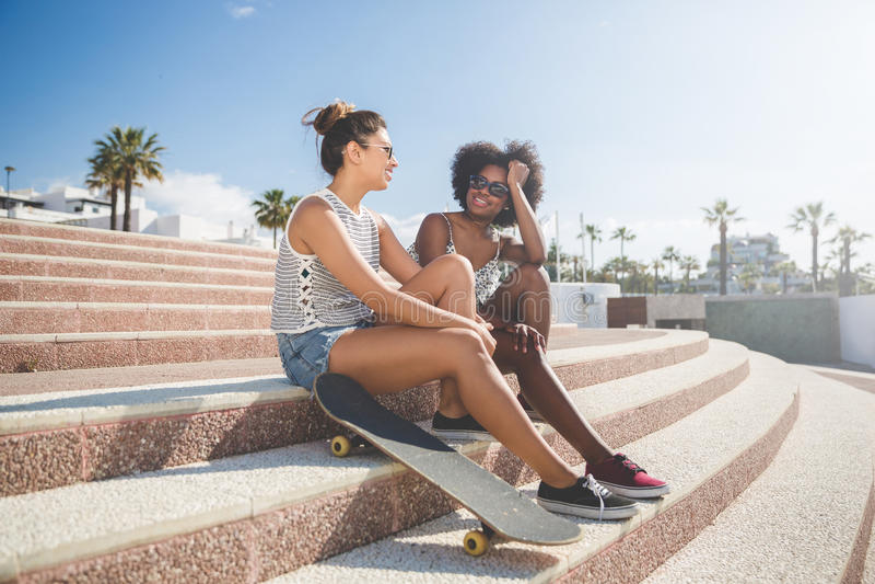 Två nätta kvinnliga vänner som sitter på trappasamtal arkivbilder