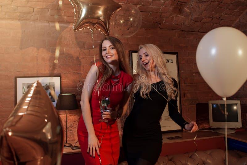 Två nätta kvinnor i coctailklänningar som poserar med ballonger på födelsedagpartiet i stilfullt kafé royaltyfri foto