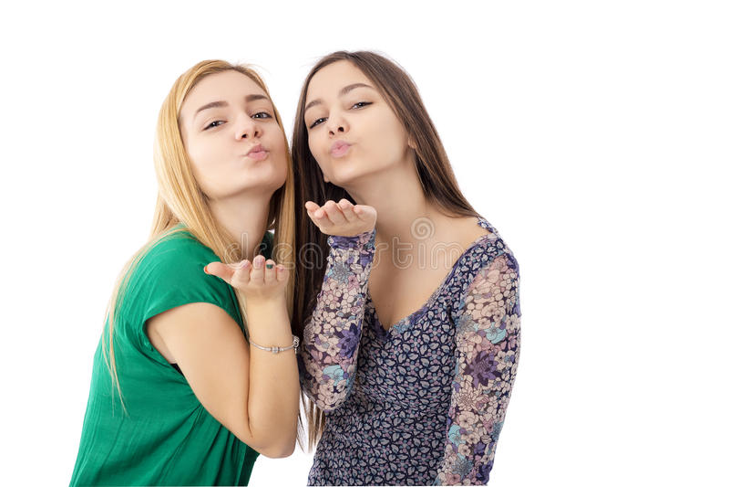 Två nätta tonårs- flickor - blondin och brunett som överför kyssar fotografering för bildbyråer
