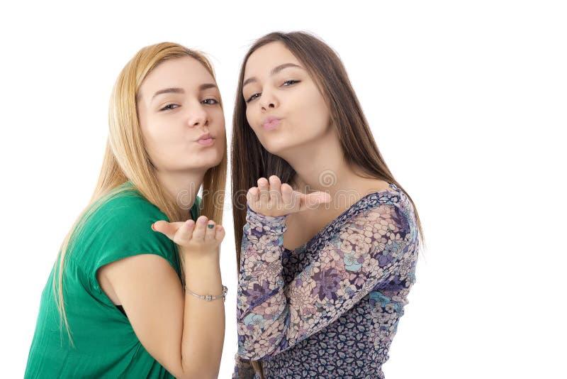 Två nätta tonårs- flickor - blondin och brunett som överför kyssar royaltyfria bilder