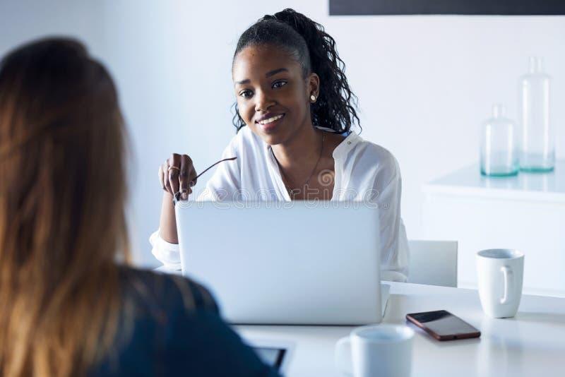Två nätta unga affärskvinnor som arbetar med den digitala minnestavlan och bärbara datorn i kontoret royaltyfri foto
