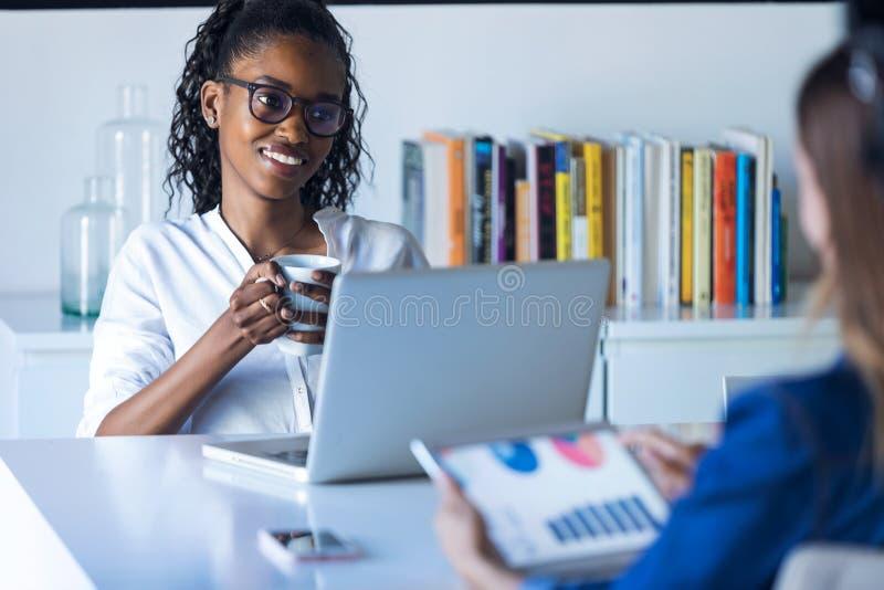 Två nätta unga affärskvinnor som arbetar med den digitala minnestavlan och bärbara datorn i kontoret royaltyfri bild