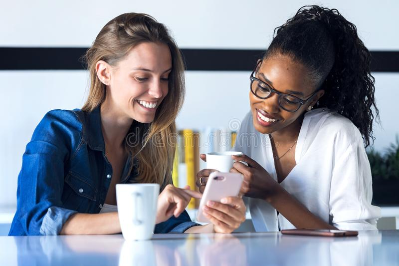 Två nätta unga affärskvinnor som tillsammans använder hennes mobiltelefon, medan ta ett avbrott i kontoret arkivfoton