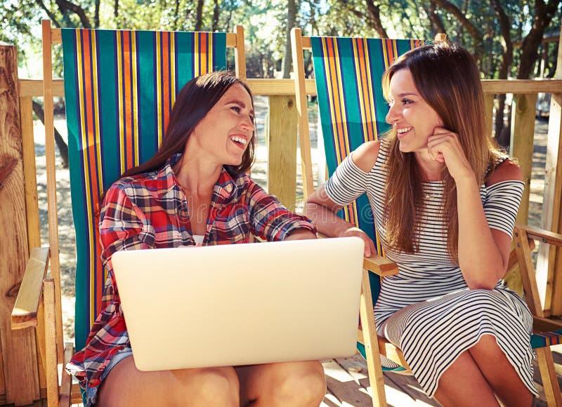 Två nätta unga kvinnor som tillsammans sitter och snackar royaltyfri foto