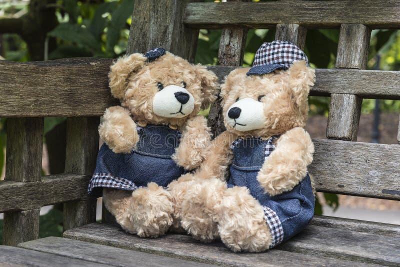 Två nallebjörnar som sitter på bänkhanden i trädgård, arkivfoton