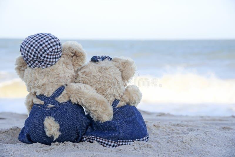 Två nallebjörnar som sitter på stranden royaltyfria foton