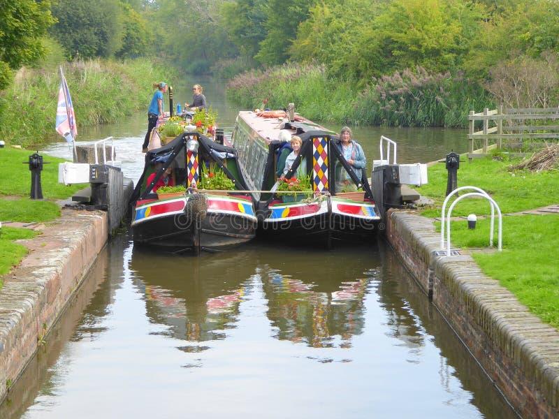 Två narrowboats som skriver in ett kanallås arkivfoto