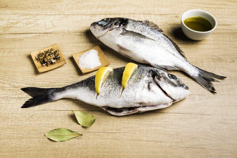 Två ny fisk Dorada med lagerbladar, några stycken av citronen, en bunke av olja och några kryddor på en trätabell arkivfoton