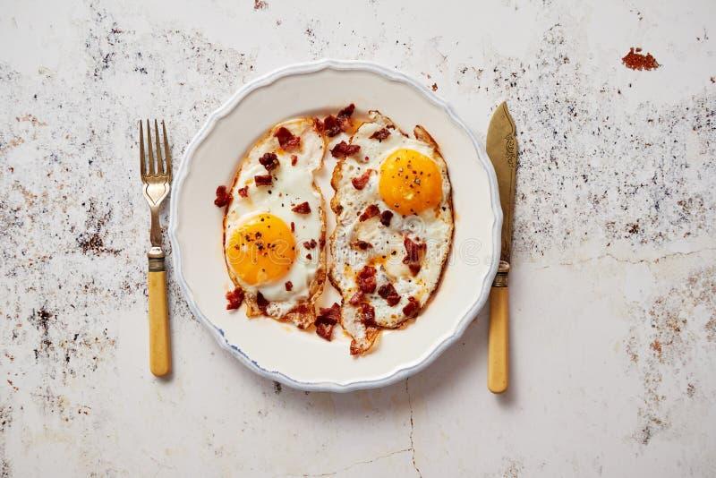 Två nya stekte ägg med frasig knaprig bacon och gräslöken tjänade som på den lantliga plattan royaltyfri fotografi