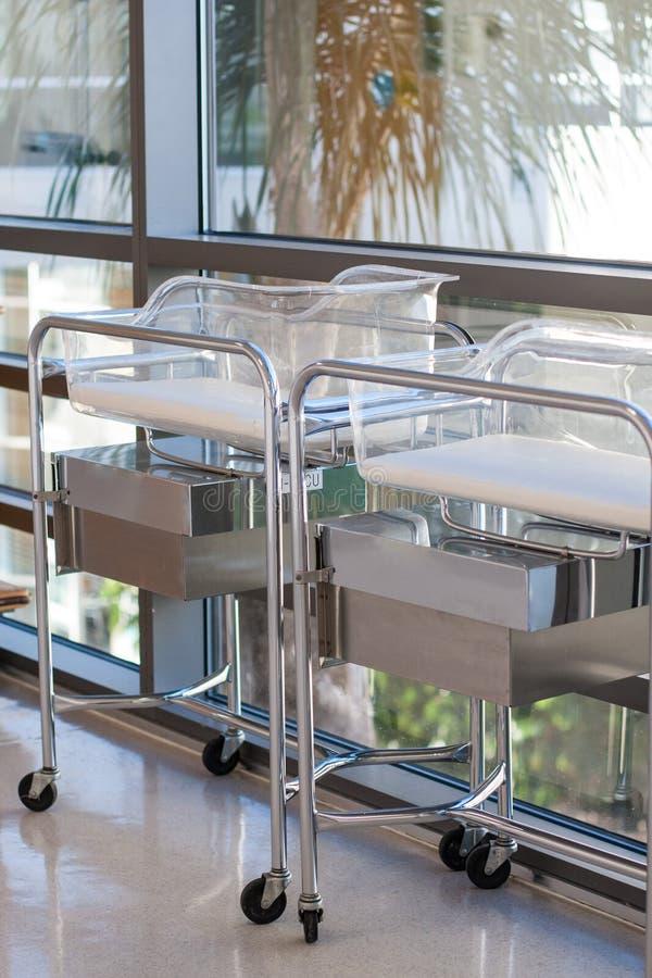 Två nyfödda babyliftar eller sängar i sjukhushall arkivfoto