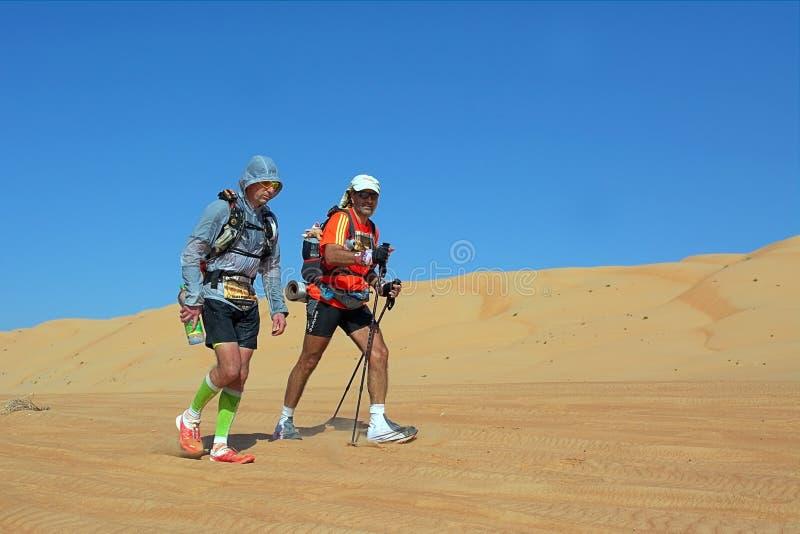 Två oidentifierade löpare som kör i den Wahiba öknen arkivfoto