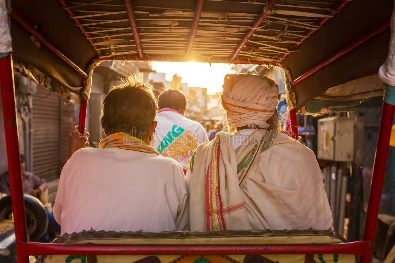 Två oidentifierade män som rider på rickshawen royaltyfria foton