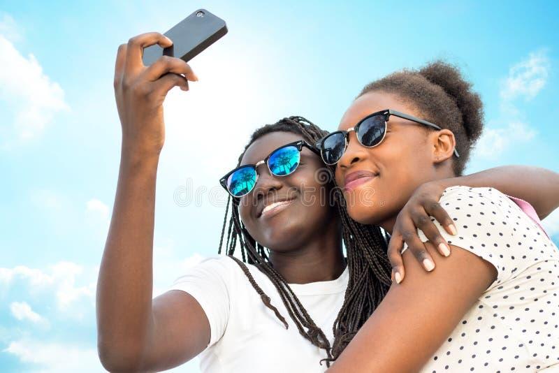 Två olika afrikanska flickor som tar självståenden med telefonen arkivbilder