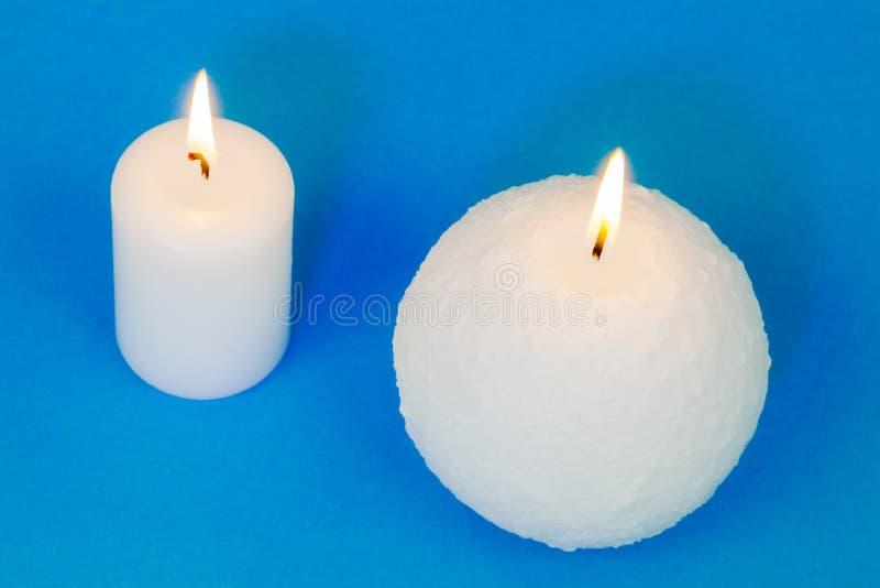 Två olika brinnande stearinljus på blå bakgrund royaltyfri fotografi