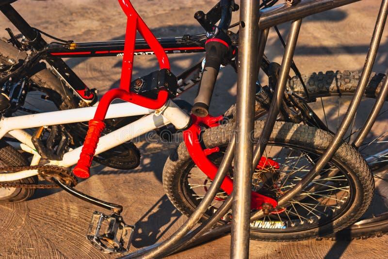 Två olika cyklar i parkeringsplatsen utanför Cykelparkering eller cykelställning arkivfoton