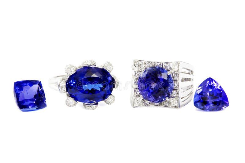 Två olika damcirklar med Tanzanite och diamanter och två Tanzanite stenar royaltyfri fotografi