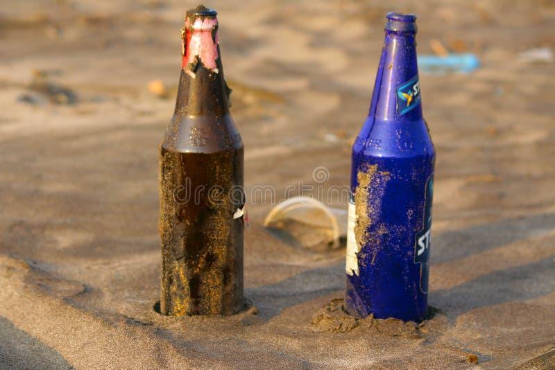 Två olika färgglasflaskor på stranden på Palande arkivbild