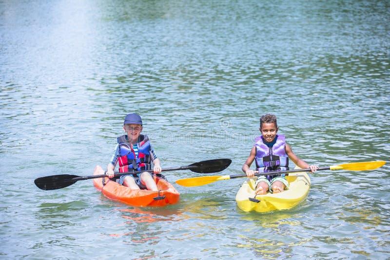 Två olika pojkar som tillsammans kayaking på sjön royaltyfria foton