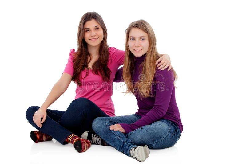 Två olika systrar som sitter på golvet arkivbilder