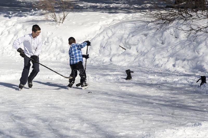 Två ortodoxa jewpojkar för hasidim som spelar hockey på is royaltyfri bild