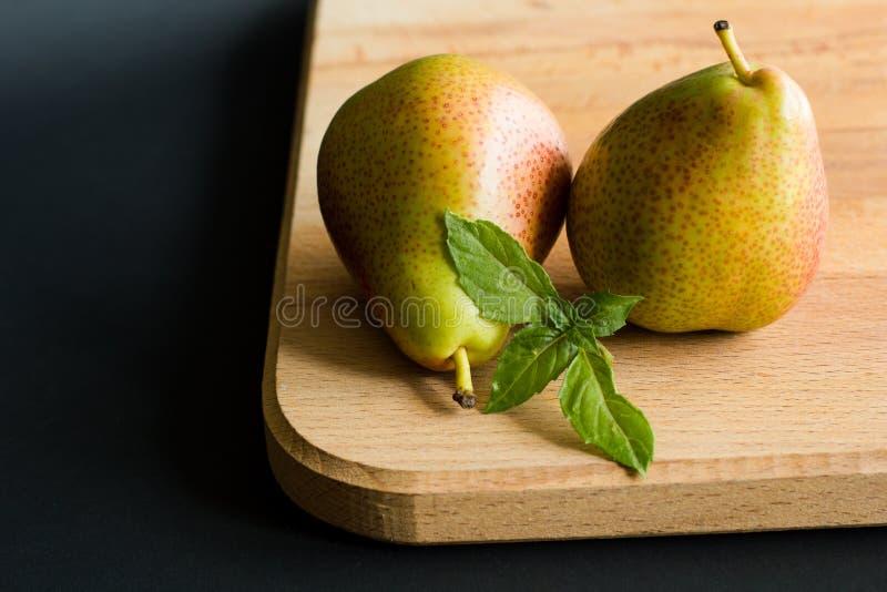 Två päron med nya basilikasidor på en träskärbräda med svart bakgrund fotografering för bildbyråer