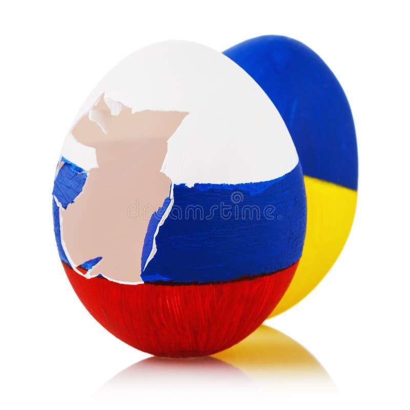 Två påskägg som målas i färg av flaggor av Ryssland och Ukraina på vit bakgrund, closeup royaltyfri bild