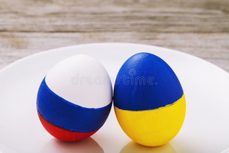 Två påskägg som målas i färgen av flaggor av Ryssland och Ukraina i en keramisk platta på en trätabell royaltyfri bild