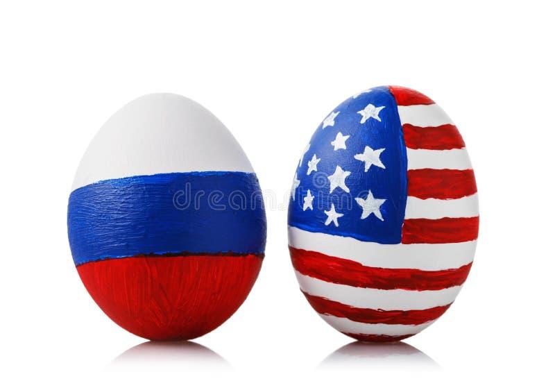 Två påskägg som målas i färger av flaggorna av Ryssland och Amerika på vit bakgrund royaltyfri bild