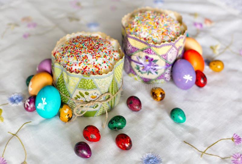 Två påskkakor med sockerglasyr och färgrika - guling, rött, violett som är grön, violet - påskägg med vita bilder arkivfoto