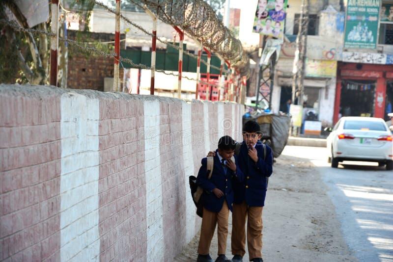 Två pakistanska skolaungar som promenerar det gränsväggen och staketet royaltyfria foton