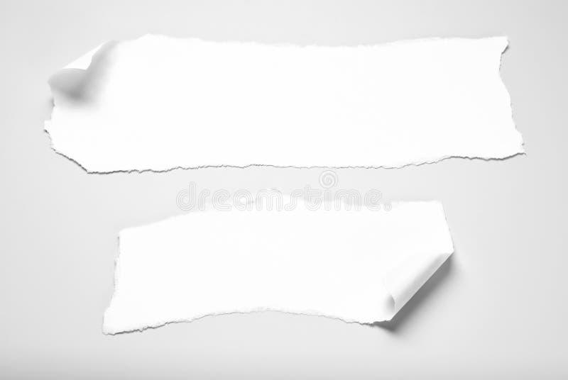 Två pappers- rester med krullade hörn arkivfoto