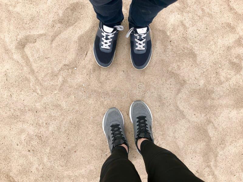 Två par av ben i gymnastikskoskoställning mitt emot de mot den naturliga lösa gula guld- varma strandsanden för bakgrund royaltyfria foton
