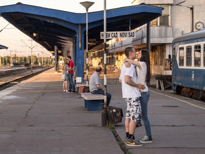 Två par av den vita caucasian mannen och kvinnlig som kysser i den Novi Sad drevstationen som väntar på drevet som ska avskilja d arkivfoton