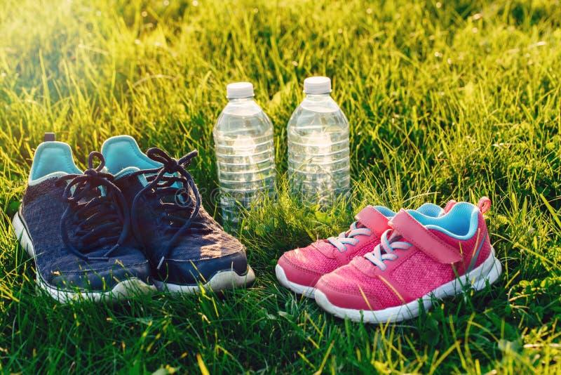 Två par av gymnastikskor och flaskor av vatten i grönt gräs utanför på solnedgång arkivbild