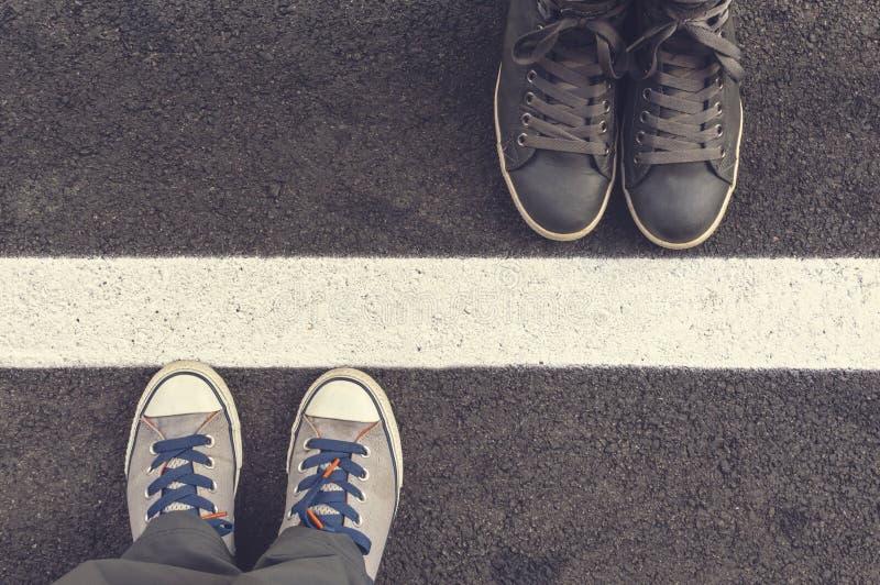 Två par av gymnastikskor på en asphaptväg arkivfoto