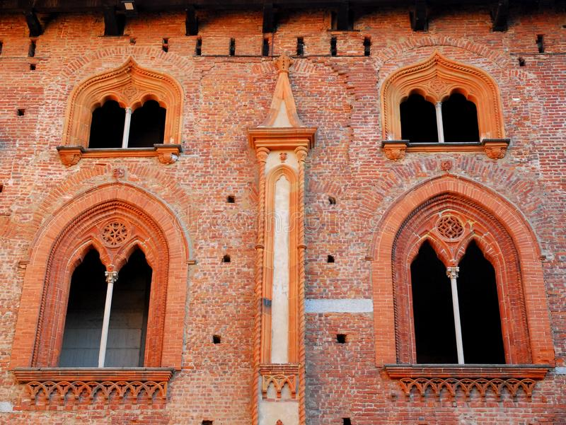 Två par av underbara spröjsade fönster i slotten av Vigevano nära Pavia i Lombardy (Italien) royaltyfri bild