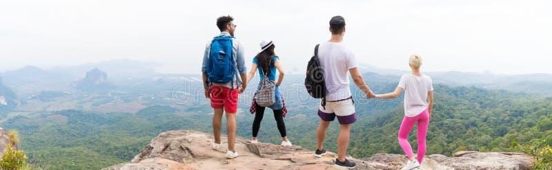 Två par med ryggsäckar som står på bergöverkant, tycker om bakre sikt för landskap tillbaka, unga män och kvinnan royaltyfria bilder