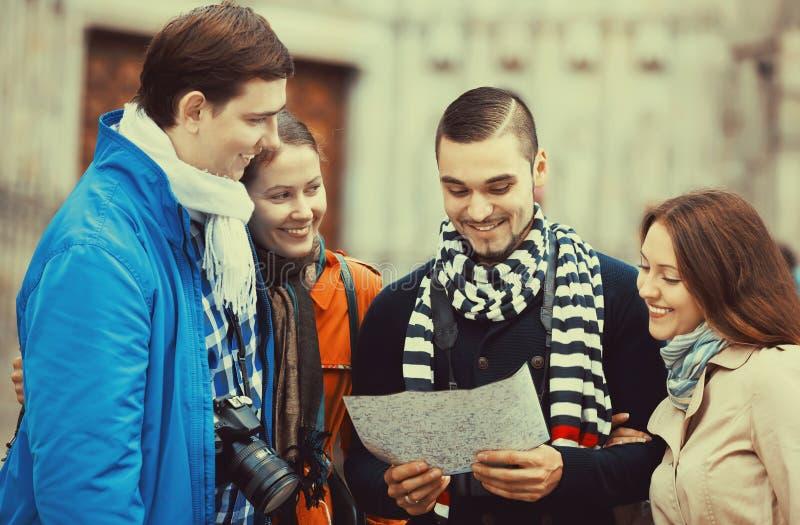 Två par som läser stadsöversikten fotografering för bildbyråer