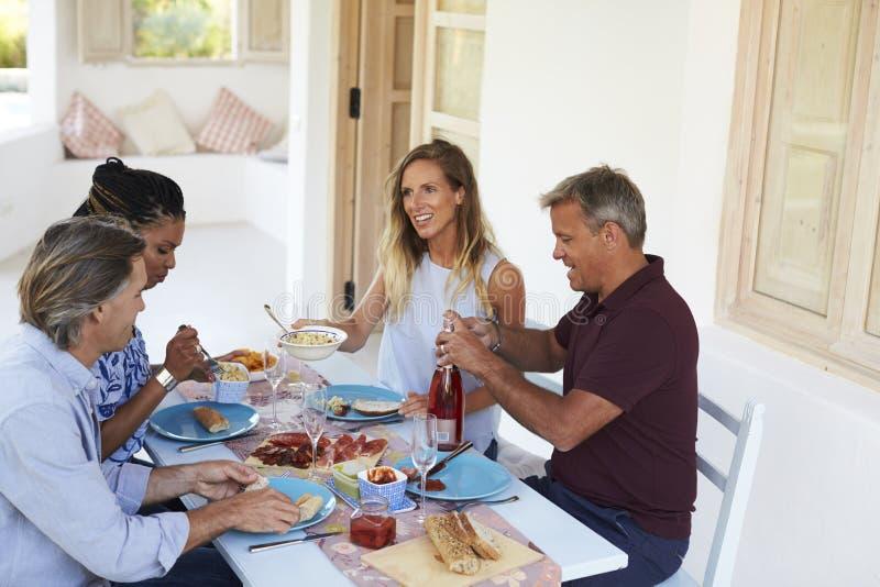 Två par som ner sitter för matställe på en tabell på en uteplats royaltyfri bild