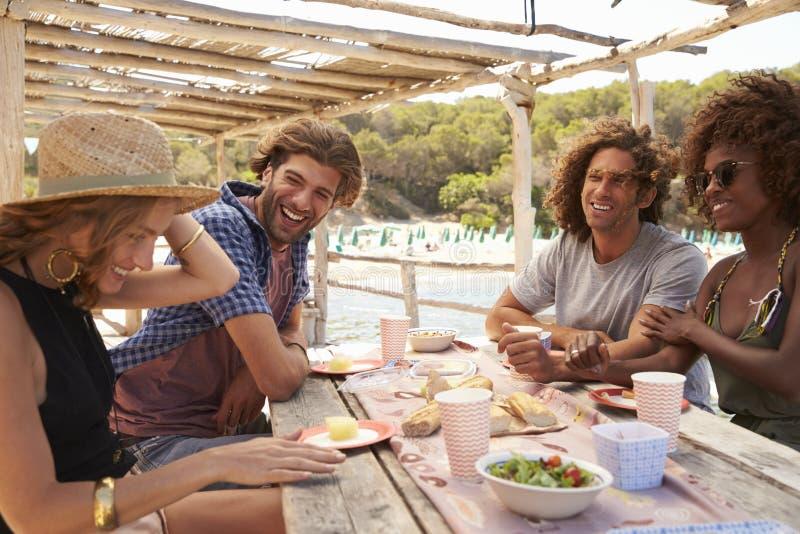 Två par som sitter på en tabell på sjösidan, Ibiza, Spanien royaltyfria foton