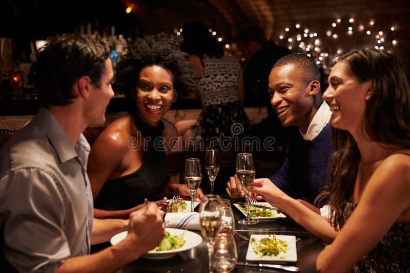 Två par som tillsammans tycker om mål i restaurang arkivbilder