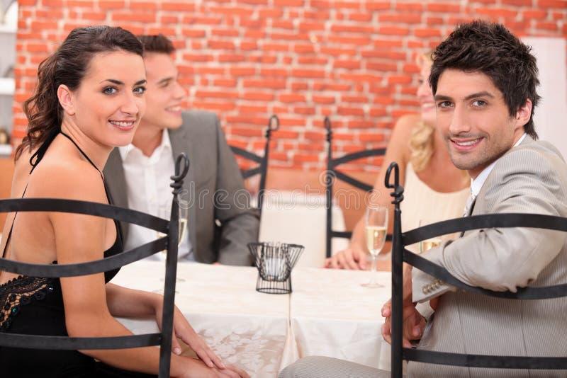Två par som ut äter middag royaltyfri foto