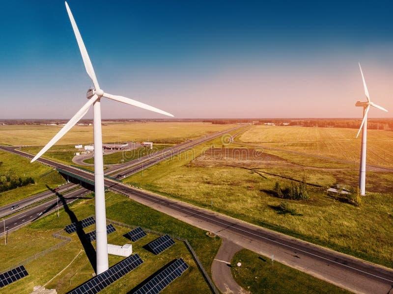 Två parallella vindstationer gjuter dag för grönt gräs och för huvudväg för skugga ljus solig royaltyfria foton